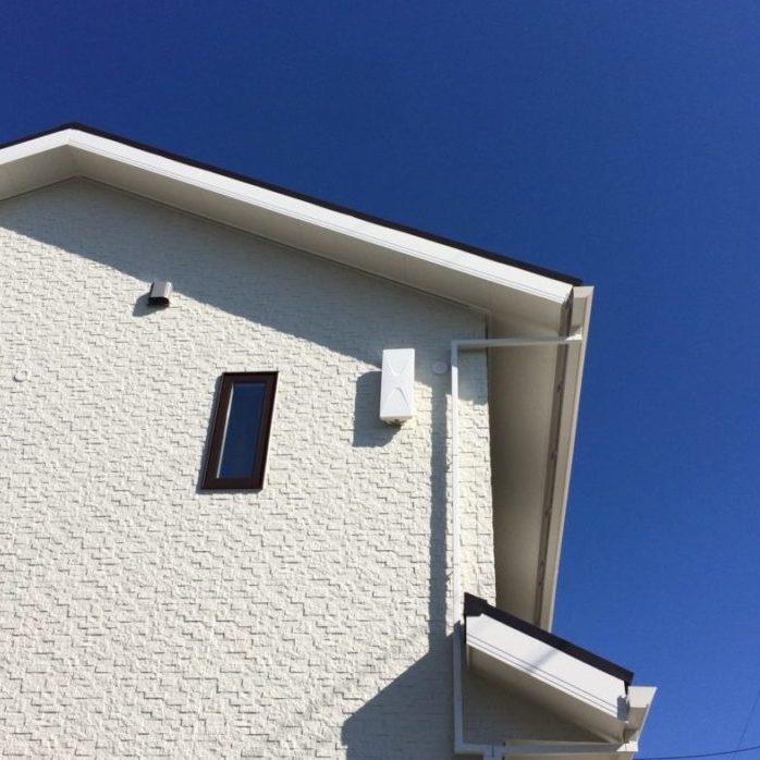 白壁の壁面に設置された白いデザインアンテナ
