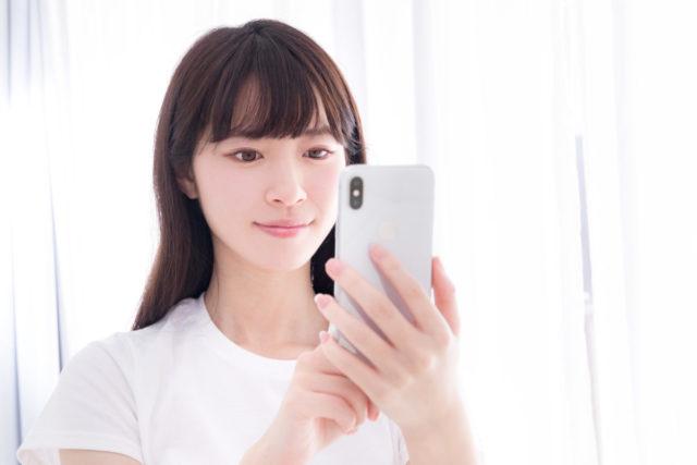 スマートフォンでポチる女性の画像