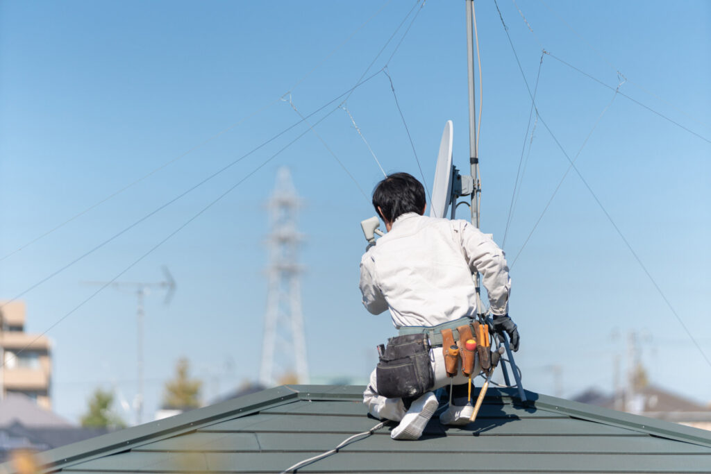 屋根の上にアンテナを設置するアンテナ職人
